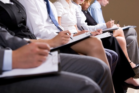 Close-up of business people making notes or writing business plan at conference