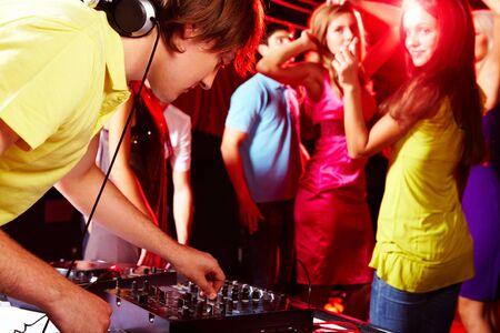 Smart deejay adjusting technics with dancing teens on background