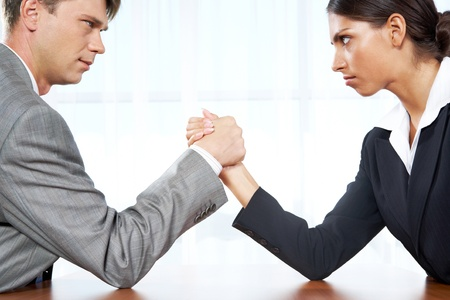 Portrait of business competitors doing arm wrestling and looking into each other's eyes