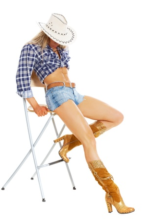 Portrait of a sexy model posing in cowgirl clothing posing on a chair