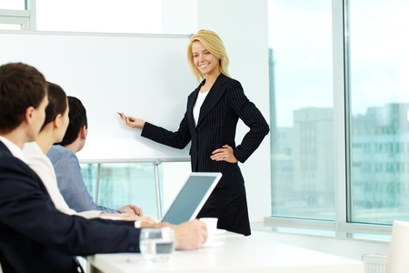Pretty manager pointing at whiteboard while colleagues listening to her