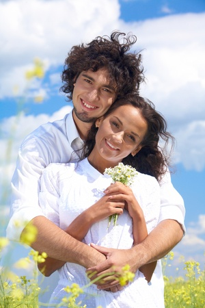 Young man hugging charming lady in white clothing while both looking at camera with happy smiles