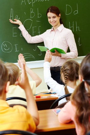 Portrait of smart teacher pointing at blackboard and looking at schoolkids in classroom