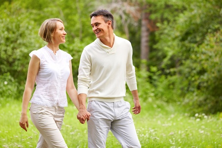 Portrait of young happy couple walking in summer park