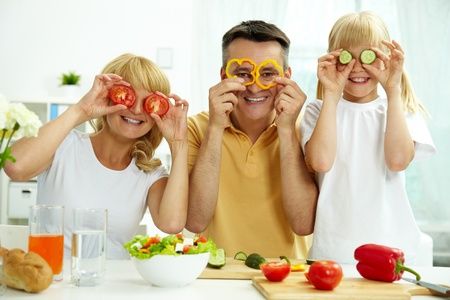 Portrait of happy parents and their daughter posing with vegetables in the kitchen