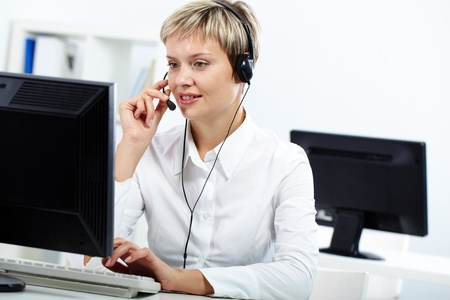 Young secretary with headset answering a call