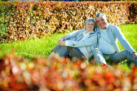 Photo of happy aged man and woman looking at camera in autumnal park