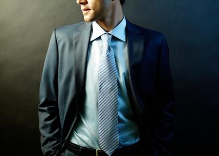 Figure of elegant businessman in suit posing in darkness