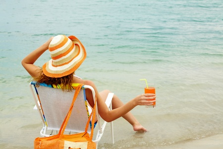 Back of restful lady holding glass with fresh juice while relaxing by water