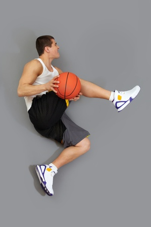 Basketball player executing a tricky jump with a ball