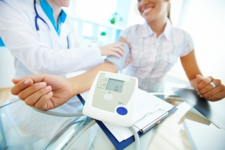 Close-up of tonometer by patient's arm during blood pressure measuring at medical consultation