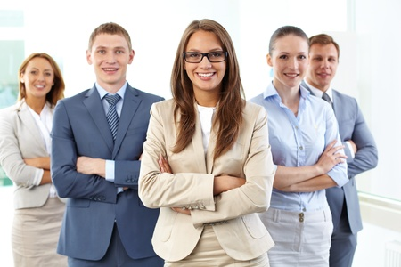 Portrait of five businesspeople looking at camera with female leader in front