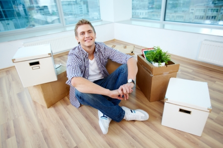 A young guy sitting on the floor of new house surrounded with boxes