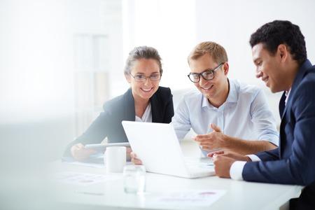 Photo pour Portrait of smart business partners using laptop at meeting - image libre de droit
