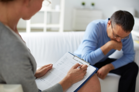 Female psychologist consulting pensive man during psychological therapy session