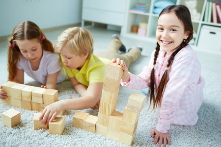 Three little friends playing with wooden bricks, happy girl looking at camera
