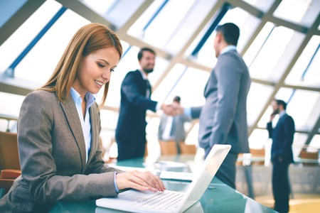 Pretty businesswoman networking or planning work on background of colleagues handshaking