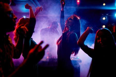 Group of dancing young people enjoying night in club