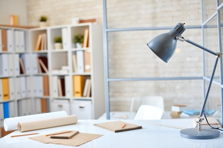 Desk with lamp, papers and pencils in office