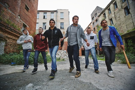 Group of spiteful hooligans walking along grunge brick houses