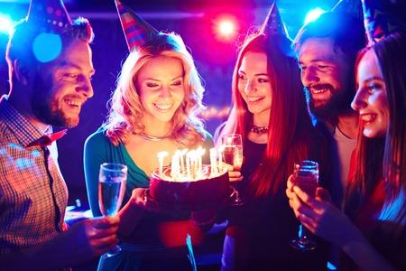Young people around birthday cake