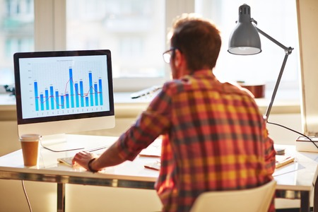 White collar worker analyzing financial chart in office