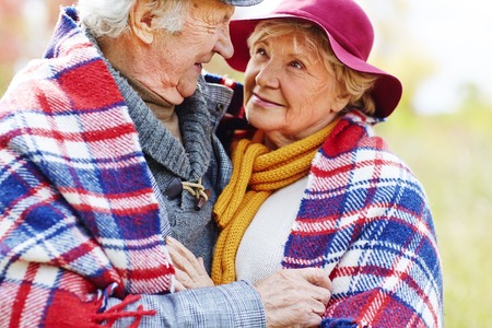 Retired couple in embrace looking at one another