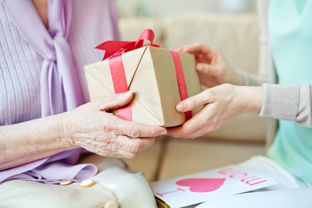 Young woman giving present to elderly one