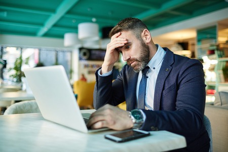 Tired businessman looking at laptop display
