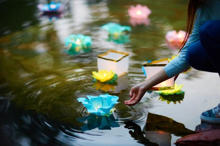 Traditional festive paper lilies with burning candles floating upon river surface