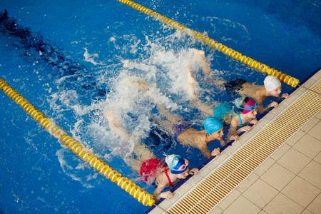Row of active children splashing water in pool