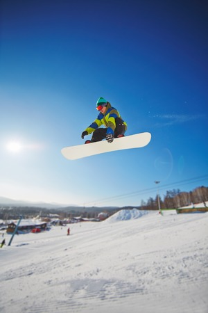 Snowboarding competitor freeriding against blue sky