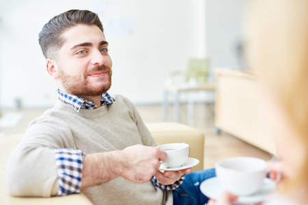 Coworkers drinking coffee on sofa