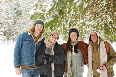 Waist up portrait of group of happy young people posing in winter resort standing under fir tree in beautiful snowy forest