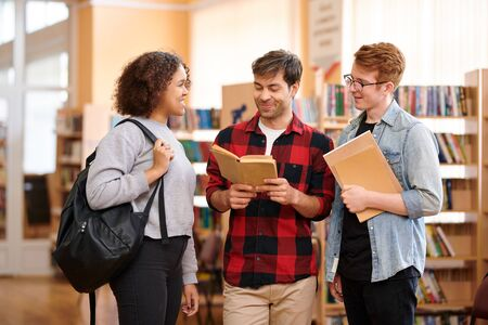 Foto de Happy casual students with books preparing for seminar or exam - Imagen libre de derechos
