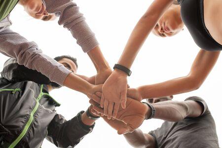 Photo pour Below angle of young intercultural sporty people maing pile of hands - image libre de droit
