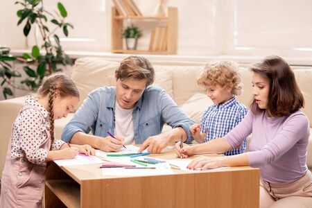 Photo pour Young family of married couple and their two little elementary age kids drawing - image libre de droit