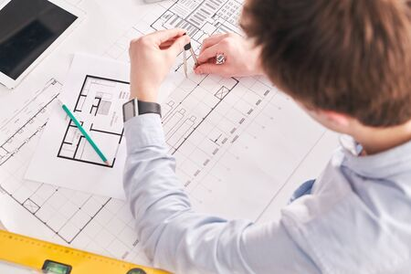 Photo pour Above view of building engineer sitting at desk and using pair of compasses while working on floor plan of flat - image libre de droit