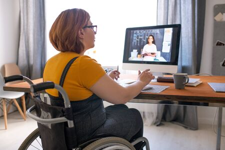 Foto de Young disabled tutor sitting in wheelchair and helping black student girl with hometask online while working remotely - Imagen libre de derechos