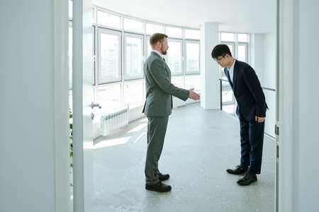 Foto de Young successful businessman in formalwear greeting Asian business partner - Imagen libre de derechos