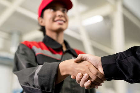Photo pour Hand of happy young female engineer in workwear handshaking with colleague - image libre de droit