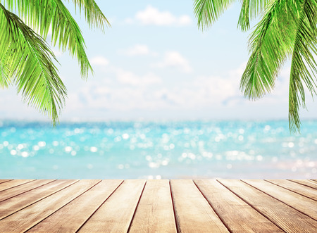 Photo for Wooden table top on blue sea and white sand beach background. Coconut palm trees against blue sky and beautiful beach in Punta Cana, Dominican Republic. Vacation holidays background wallpaper. - Royalty Free Image