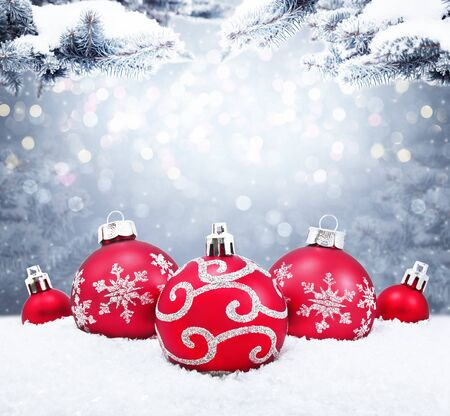 Photo pour Beautiful red Christmas balls on the red background. Christmas ornament on snow with fir branches. - image libre de droit