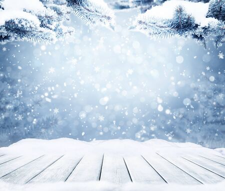 Photo pour Winter decorative Christmas background with bokeh lights, snowflakes and empty old wooden table. Christmas and Happy New Year blue background with snowflake. Winter landscape with falling snow and fir tree branches. - image libre de droit
