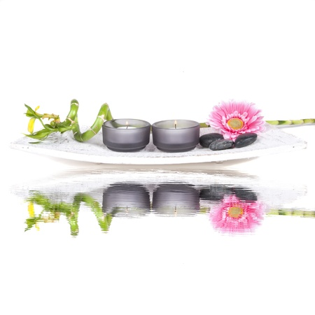 Spa set with pink flower, candles and bamboo on a white background