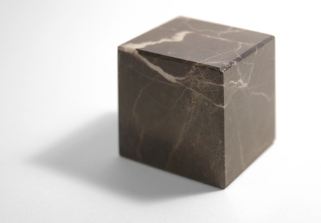 studio photography of a marbled reddish stone cube isolated on white with shadow