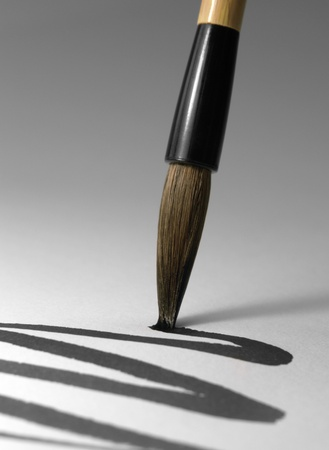 detail of a chinese brush while drawing a line in light back