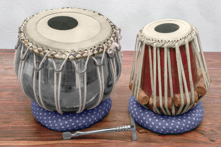 set of traditional tabla drums on wooden surface