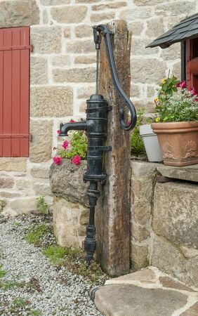 black historic water pump seen in Brittany, France