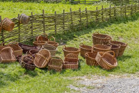 lots of wicker baskets near a rural wooden fence
